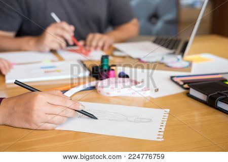 Two Young Professional Fashion Designer Colleagues Working And Project Of Drawing Sketches For Cloth