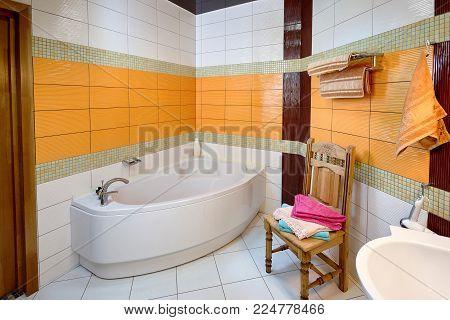 Interior of Bathroom Room with Bath in Orange Tones