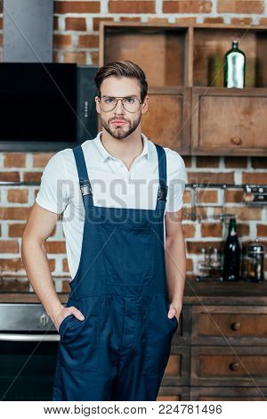portrait of handsome young repairman in protective workwear looking at camera