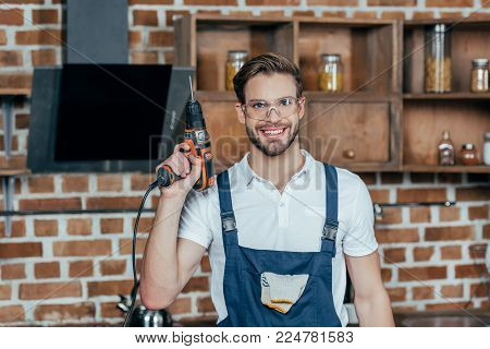 young repairman in protective workwear holding electric drill and smiling at camera