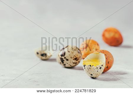 Easter greeting card with colored yellow orange quail eggs with yolk and shell over white texture background. Close up, copy space. Toned image