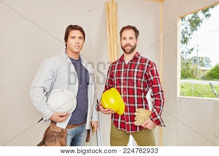 Two men as craftsman team working at construction
