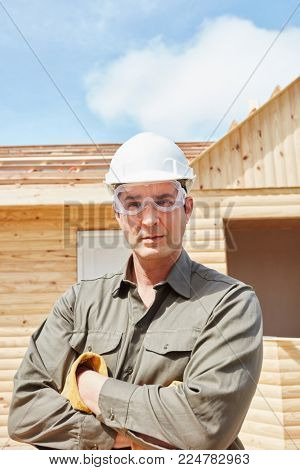 Skilled blue collar worker at construction site building new woodhouse