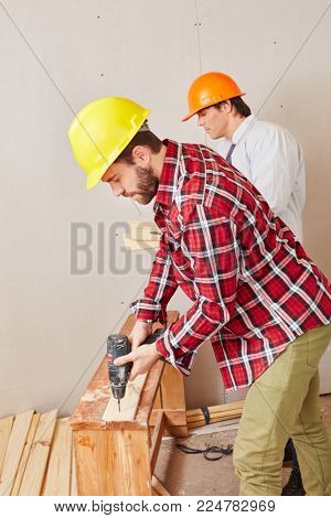 Carpenter working with competence using drilling machine on wood