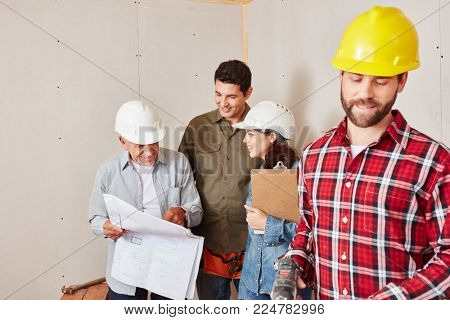 Craftsmen group as a team planning with architectural drawing