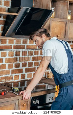 young repairman in protective workwear leaning at oven in kitchen