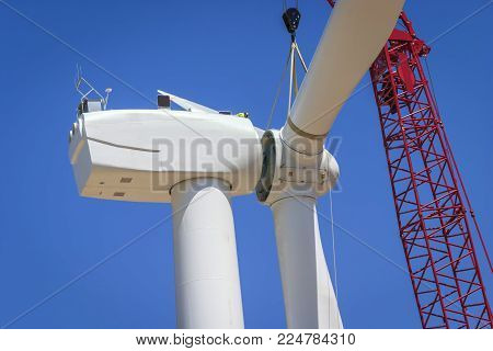 Wind turbine rotor assembly being attached to the generator unit by a large crane.