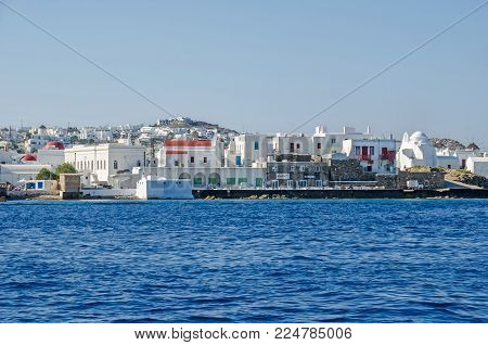Panoramic vew of Mykonos town (Chora) from the Aegean Sea with its waterfront, white buildings representatives of tourism driven Cycladic architecture, and whitewashed Panagia Paraportiani - the Church of Our Lady - to the right.