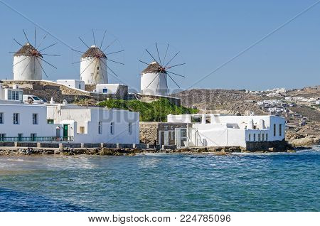 View of windmills of Mykonos town (Chora) from the Aegean Sea, capped with wood and straw, built by the Venetians in the 16th century. Greece.