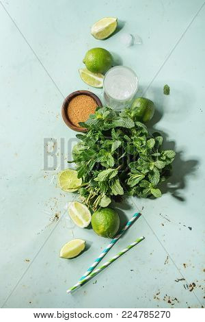 Ingredients for making mojito cocktail. Bundle of fresh mint, whole and sliced limes, brown sugar, crashed ice cubes, glass of soda water, cocktail tubes over green pin up background. Top view, space