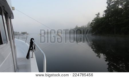 a quiet morning on the boat, in the mist, on a glassy lake, in an anchorage