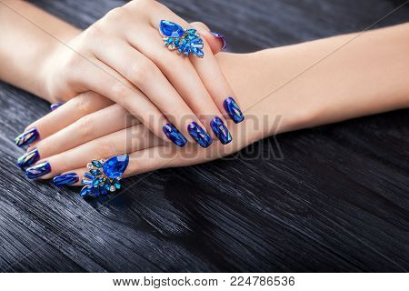 Shattered glass blue manicure on black wooden background