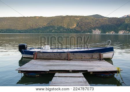 Wooden pontoon on Danube river shore going to fishing boat. Mountains on background at sunset.