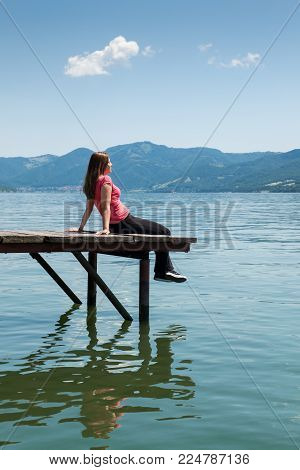 A young woman in red blouse sitting on a pontoon on a river shore.
