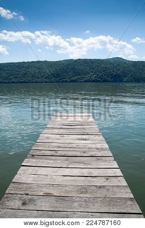 Wooden pontoon on Danube river shore with mountains on background at sunset.