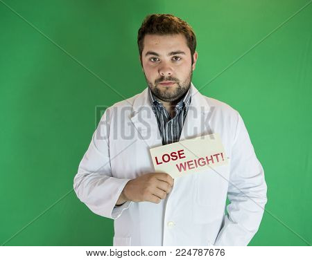 Young nutritionist in white robe with Lose Weight sign in hand
