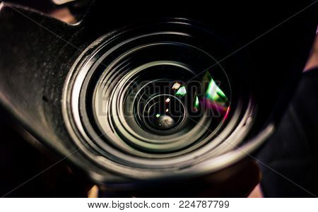 Camera lens closeup with light reflection and blurred background