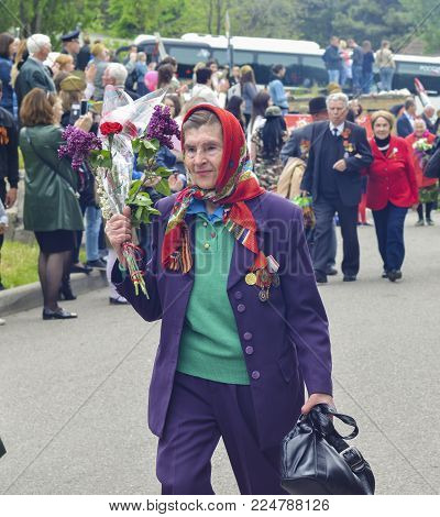PYATIGORSK, RUSSIA - MAY 09, 2017: War veteran woman with flowers on the Victory Day celebration. Russian babushka
