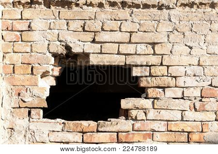 Damaged brick wall of house or building with hole destroyed by grenade in the war zone