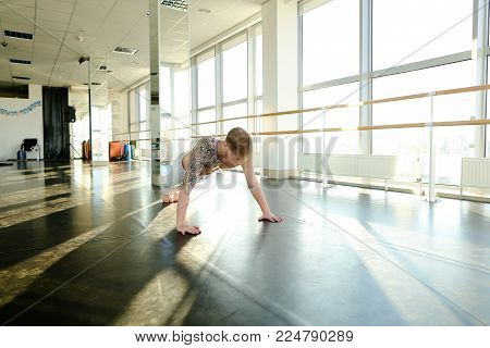 Model diligently rock press, tattooed guy try to keep fit. Handsome male with good body lie on floor in spacious well-equipped hall with big windows and mirrors. Concept of sportswear, gym for trainings or individual workouts