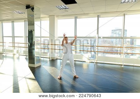 Economist dance and fool for camera in gym, young tattooed man making video broadcast. Positive guy with mustache wearing white T-shirt and sport trousers energetically moving on parquet floor. Concept of big hall for workouts, sportswear or individual tr