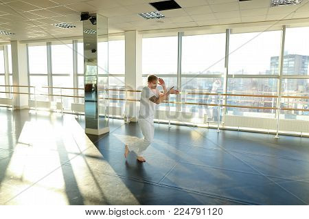 Hip-hop dancer rehearse before performance on charity event, tattooed male moving energetically. Fair-haired guy with mustache in big gym with ballet barre. Concept of choreographic school, dancing courses or comfortable sport clothes