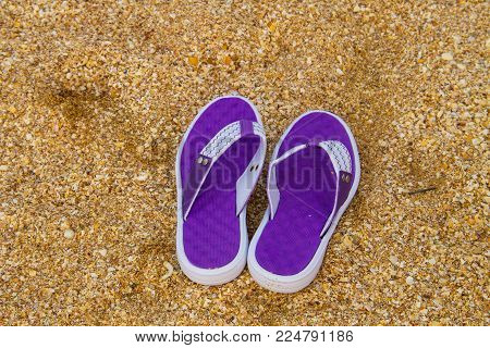 Pair of flip flops on a sandy sea beach. Summer vacation concept
