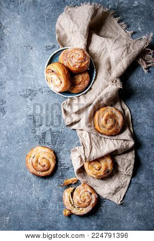 Homemade glazed puff pastry cinnamon rolls with custard and raisins on textile linen over blue texture background. Top view, space