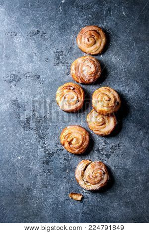 Homemade glazed puff pastry cinnamon rolls with custard and raisins over blue texture background. Top view, space