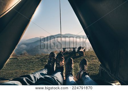 First they see in the morning. Close up of young couple enjoying the view of mountain range while lying in their tent