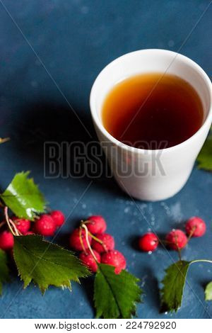 Close up white cup with tea and red hawberries healthy vitamin drink