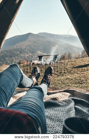 Real relaxation. Close up of woman holding mug while enjoying the view of mountain range from the tent