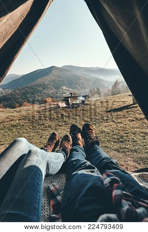 Traveling with beloved. Close up of young couple enjoying the view of mountain range while lying in the tent