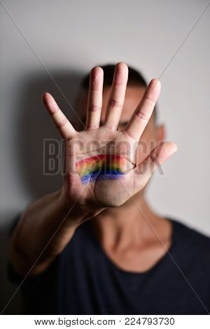closeup of a young caucasian man with the palm of his hand in front of his face with a rainbow flag painted in it