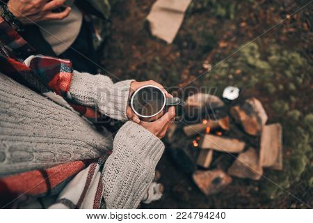 Have a hot coffee and move on. Close up top view of young couple resting while warming up near the campfire