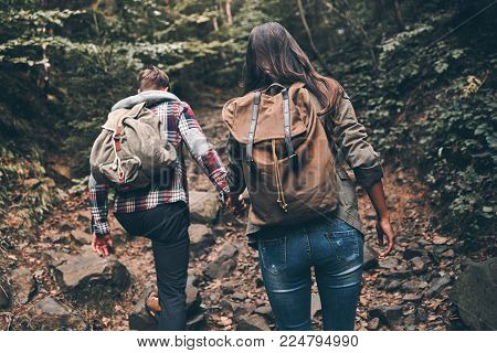 Sometimes hiking is very hard. Rear view of modern young couple holding hands and moving up while hiking together in the woods