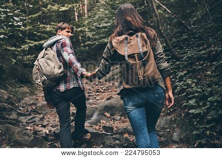 Enjoying the travel. Rear view of modern young couple holding hands and moving up while hiking together in the woods