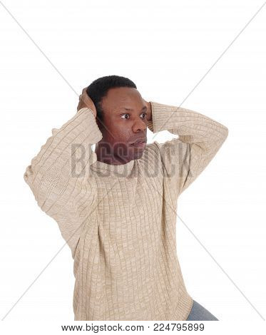 A young African American man looking horrified and scary with his hands on his head and big eyes, isolated for white background