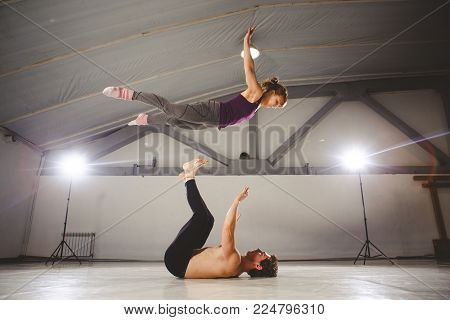 The theme of Acroyoga and Yoga Poses. Acroyogis practicing. with studio Backlight. the Base man tosses the Pops woman Flyer in flight up. Position Acrobatic flying.