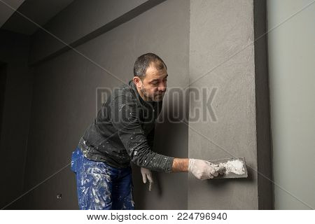 Real construction worker painting wall using plasterer.