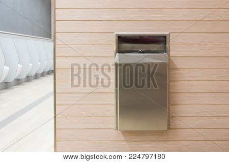 Tissue Paper And Trash Bin On Wooden Wall At Public Toilet