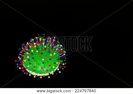 Pincushion with pins with colored head on black background.