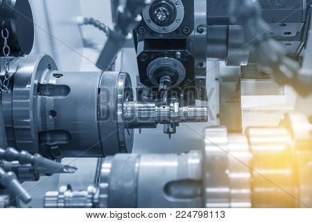 The  CNC lathe milling the steel shaft .The  modern machining process.