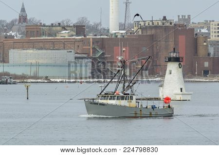 New Bedford, Massachusetts, USA - February 1, 2018: Commercial fishing boat Alison Rose, hailing port Little Compton, Rhode Island, passing Palmer's Island lighthouse in New Bedford harbor