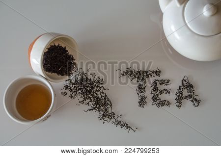 Tea concept with tea pot and cups and word tea made of tea leaves on the white table.