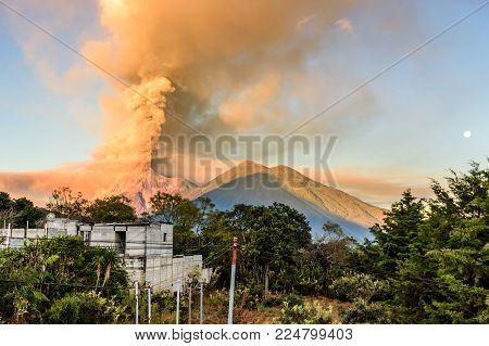 Fuego volcano erupting at dawn next to Acatenango volcano with super blue moon, near Antigua, Guatemala, Central America