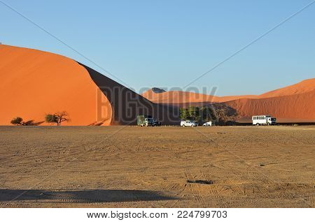 Sossusvlei, Namibia - JAN 29, 2016: Tourists cars near Dune No.45 at sunrise, most popular dune in the whole World, Namibia, Africa