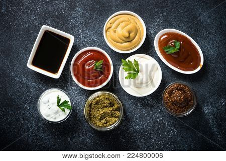 Set of sauces - ketchup, mayonnaise, mustard soy sauce, bbq sauce, pesto, mustard grains and pomegranate sauce on dark stone or metal background. Top view.