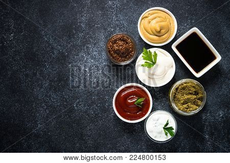 Set of sauces - ketchup, mayonnaise, mustard soy sauce, bbq sauce, pesto, mustard grains and pomegranate sauce on dark stone or metal background. Top view with copy space.
