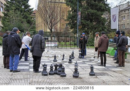 Sarajevo, Bosnia and Herzegovina - December 18, 2017: men are playing chess with huge figures outdoor in Sarajevo, Bosnia and Herzegovina